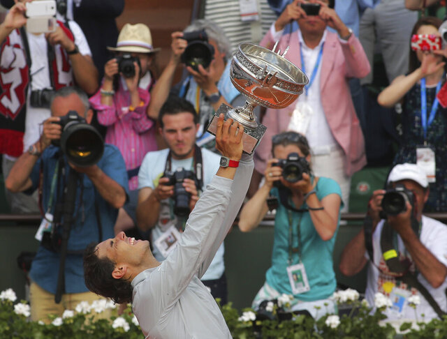 FILE - In this June 8, 2014, file photo, Spain's Rafael Nadal holds the trophy after winning the final of the French Open tennis tournament against Serbia's Novak Djokovic at Roland Garros stadium, in Paris. Nadal will be trying to win his record-extending 13th championship at the clay-court major tournament when play begins on Sunday,  Sept. 27, 2020 (AP Photo/Thibaut Camus, File)