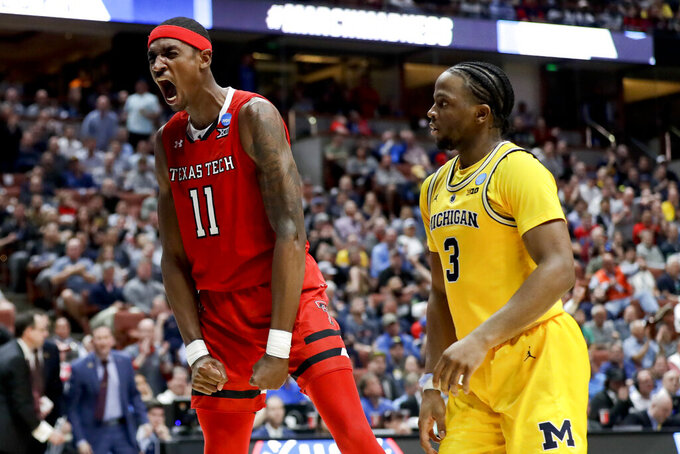Texas Tech forward Tariq Owens -celebrates after scoring as Michigan guard Zavier Simpson watches during the second half an NCAA men's college basketball tournament West Region semifinal Thursday, March 28, 2019, in Anaheim, Calif.(AP Photo/Marcio Jose Sanchez)