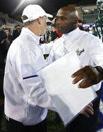 Tulsa coach Philip Montgomery, left, and South Florida coach Charlie Strong meet following an NCAA college football game in Tulsa, Okla., Friday, Oct. 12, 2018. (AP Photo/Sue Ogrocki)