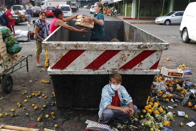 """Fabian Ramirez, 11, scavenges a trash container for vegetables with his family that were discarded at the """"Mercado de Abasto,"""" a market for vendors, during the fourth week of a quarantine to help contain the spread of the new coronavirus in Asuncion, Paraguay, Thursday, April 2, 2020. COVID-19 causes mild or moderate symptoms for most people, but for some, especially older adults and people with existing health problems, it can cause more severe illness or death. (AP Photo/Jorge Saenz)"""