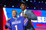 Miami edge rusher Gregory Rousseau, right, holds a team jersey with NFL Commissioner Roger Goodell after  the Buffalo Bills selected Rousseau with the 30th pick in the first round of the NFL football draft Thursday April 29, 2021, in Cleveland. (AP Photo/Tony Dejak)