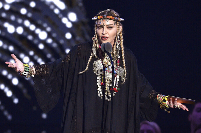 FILE - In this Aug. 20, 2018 file photo, Madonna presents a tribute to Aretha Franklin at the MTV Video Music Awards at Radio City Music Hall in New York. Eurovision Song Contest organizers said on Sunday, May 19, 2019,  they were taken aback by the display of a Palestinian flag during Madonna's guest appearance, which defied contest rules. While Madonna performed her new single at the contest, hosted in Tel Aviv, two of her dancers onstage flashed Israeli and Palestinian flags pinned on their backs. The European Broadcast Union, or EBU, said that Madonna had not cleared that part of the act with broadcasters and