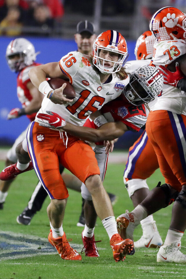 Ohio State cornerback Shaun Wade, right, tackles Clemson quarterback Trevor Lawrence during the first half of the Fiesta Bowl NCAA college football playoff semifinal Saturday, Dec. 28, 2019, in Glendale, Ariz. Wade was ejected from the game for targeting. (AP Photo/Rick Scuteri)