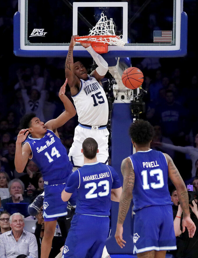 Villanova forward Saddiq Bey (15) dunks as Seton Hall guard Jared Rhoden (14), forward Sandro Mamukelashvili (23) and guard Myles Powell (13) watch during the second half of an NCAA college basketball game in the championship of the Big East Conference tournament, Saturday, March 16, 2019, in New York. Villanova won 74-72. (AP Photo/Julio Cortez)