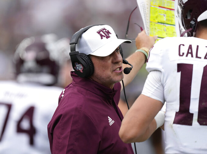 Texas A&M head coach Jimbo Fisher confers with quarterback Zach Calzada in the first half of an NCAA college football game against Colorado, Saturday, Sept. 11, 2021, in Denver. (AP Photo/David Zalubowski)