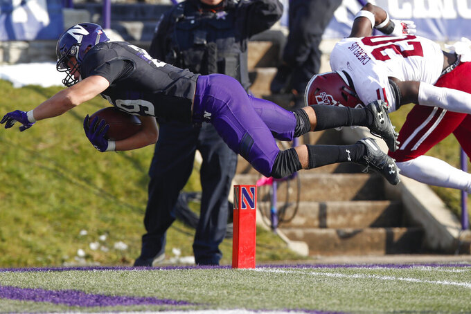 Northwestern's Evan Hull, left, scores a touchdown after being hit by Massachusetts's Claudin Cherrelus during the second half of an NCAA college football game Saturday, Nov. 16, 2019, in Evanston, Ill. (AP Photo/Jim Young)
