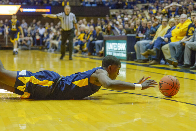 West Virginia Mountaineers forward Lamont West (15) slides to catch the ball from going out of bounds during the first half of an NCAA college basketball game in Morgantown, W.Va. on Saturday Feb. 9, 2019. (AP Photo/Craig Hudson)