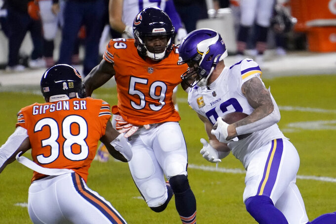 Minnesota Vikings tight end Kyle Rudolph, right, runs with the ball before fumbling for a turnover as Chicago Bears linebacker Danny Trevathan (59) and safety Tashaun Gipson Sr. (38) defend during the first half of an NFL football game Monday, Nov. 16, 2020, in Chicago. The Bears recovered the fumble. (AP Photo/Charles Rex Arbogast)
