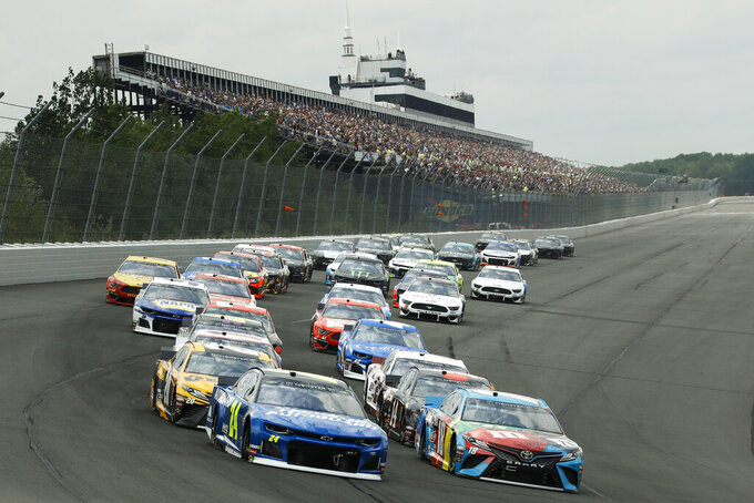 Drivers enter Turn 1 after taking the green flag to start a NASCAR Cup Series auto race at Pocono Raceway, Sunday, June 2, 2019, in Long Pond, Pa. (AP Photo/Matt Slocum)