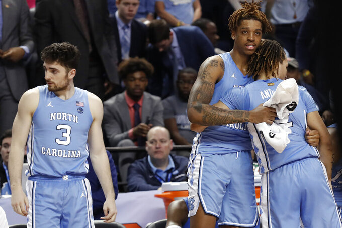 North Carolina forward Armando Bacot hugs North Carolina guard Cole Anthony while North Carolina guard Andrew Platek (3) looks awayt during the second half of an NCAA college basketball game against Syracuse at the Atlantic Coast Conference tournament in Greensboro, N.C., Wednesday, March 11, 2020. Syracuse won 81-53. (AP Photo/Gerry Broome)