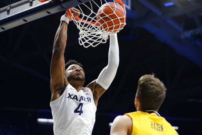 Xavier's Tyrique Jones (4) dunks as Lipscomb's Parker Hazen, right, looks on during the first half of an NCAA college basketball game, Saturday, Nov. 30, 2019, in Cincinnati. (AP Photo/John Minchillo)