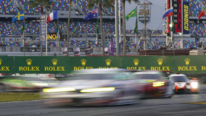 Race cars speed through the east horseshoe turn during the Rolex 24 hour auto race at Daytona International Speedway, Saturday, Jan. 30, 2021, in Daytona Beach, Fla. (AP Photo/John Raoux)