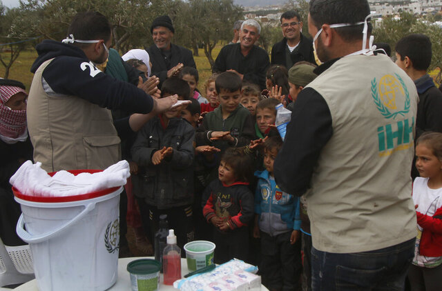 In this photo released by the Turkish humanitarian group IHH on Monday, April 6, 2020, aid workers of the group demonstrate to Syrian children how to properly wash hands, at a camp for internally displaced persons in northern Syria. The Islamic humanitarian foundation tutored children and adults on preventative measures to avoid infection by the new coronavirus and also distributed aid and personal hygiene supplies.  (IHH via AP)