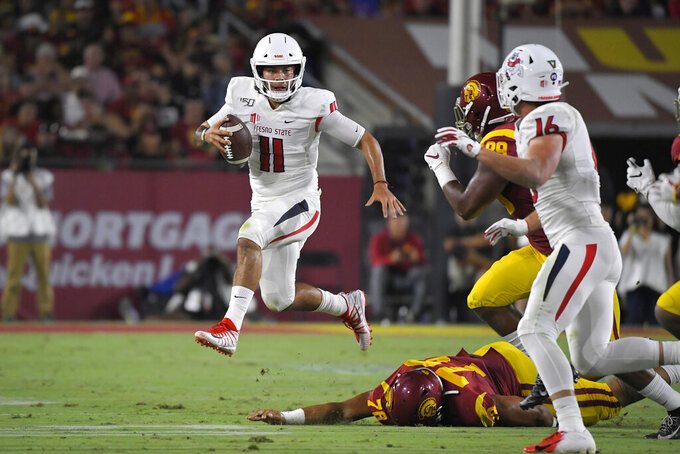 Fresno State quarterback Jorge Reyna, left, escapes a tackle by Southern California defensive lineman Jay Tufele, below, as defensive lineman Christian Rector, second from right, gives chase and tight end Jared Rice runs in during the first half of an NCAA college football game Saturday, Aug. 31, 2019, in Los Angeles. (AP Photo/Mark J. Terrill)