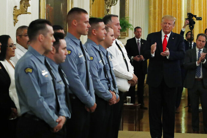 President Donald Trump applauds during a Medal of Valor and Heroic Commendations ceremony for six Dayton, Ohio police officers in the East Room of the White House, Monday, Sept. 9, 2019, in Washington, for stopping a mass shooter in August, in Dayton. (AP Photo/Alex Brandon)
