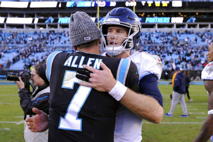 Carolina Panthers quarterback Kyle Allen (7) and Tennessee Titans quarterback Ryan Tannehill (17) hug following an NFL football game in Charlotte, N.C., Sunday, Nov. 3, 2019. (AP Photo/Mike McCarn)
