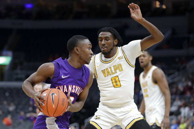 Evansville's Jawaun Newton, left, heads to the basket as Valparaiso's Javon Freeman-Liberty (0) defends during the first half of an NCAA college basketball game in the first round of the Missouri Valley Conference men's tournament Thursday, March 5, 2020, in St. Louis. (AP Photo/Jeff Roberson)