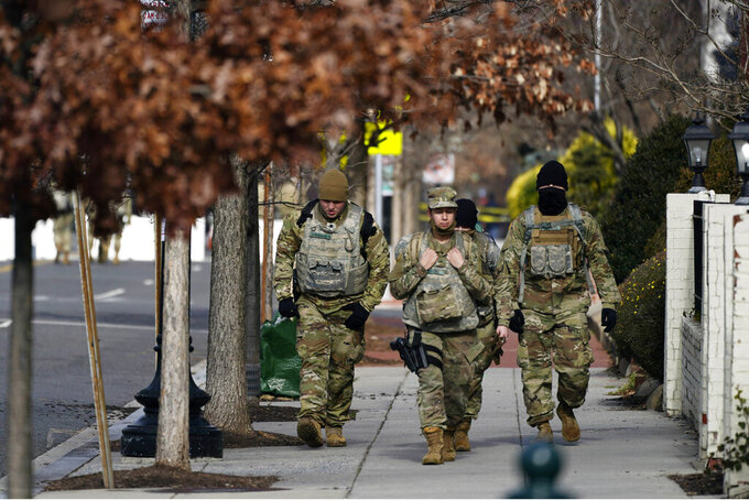National Guard walk near the Capitol as security is increased ahead of the inauguration of President-elect Joe Biden and Vice President-elect Kamala Harris, Sunday, Jan. 17, 2021, in Washington, Sunday, Jan. 17, 2021. (AP Photo/Julio Cortez)