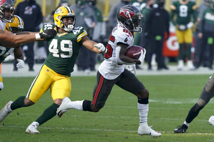 Tampa Bay Buccaneers' Jaydon Mickens (85) is chased down by Green Bay Packers' Dominique Dafney during the opening kickoff for the NFC championship NFL football game in Green Bay, Wis., Sunday, Jan. 24, 2021. (AP Photo/Morry Gash)