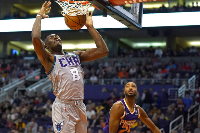 Charlotte Hornets center Bismack Biyombo dunks over Phoenix Suns forward Mikal Bridges (25) during the first half of an NBA basketball game Sunday, Jan. 12, 2020, in Phoenix. (AP Photo/Rick Scuteri)