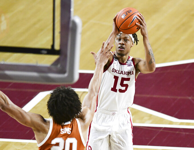 Oklahoma guard Alondes Williams (15) shoots the ball over Texas forward Jericho Sims (20) during the second half of an NCAA college basketball game in Norman, Okla., Thursday, March 4, 2021. (AP Photo/Kyle Phillips)