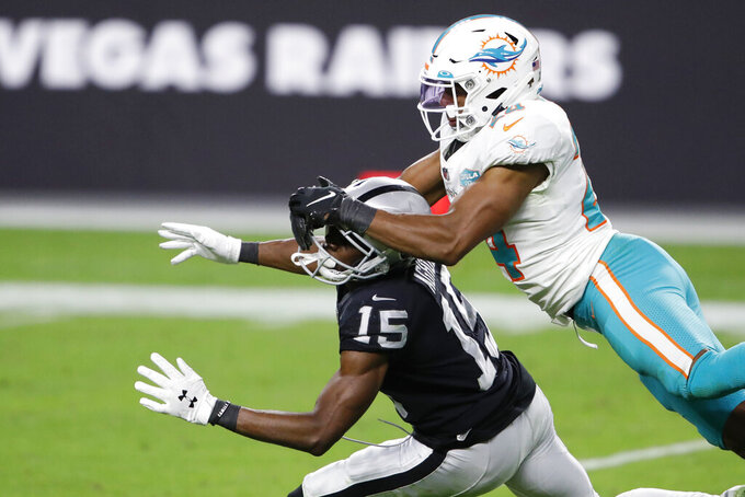 Miami Dolphins cornerback Byron Jones (24) commits a pass interference penalty on Las Vegas Raiders wide receiver Nelson Agholor (15) during the second half of an NFL football game, Saturday, Dec. 26, 2020, in Las Vegas. (AP Photo/Steve Marcus)
