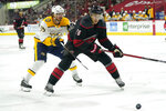 Nashville Predators center Matt Duchene (95) and Carolina Hurricanes defenseman Cavan Fitzgerald (76) chase the puck during the first period in Game 1 of an NHL hockey Stanley Cup first-round playoff series in Raleigh, N.C., Monday, May 17, 2021. (AP Photo/Gerry Broome)