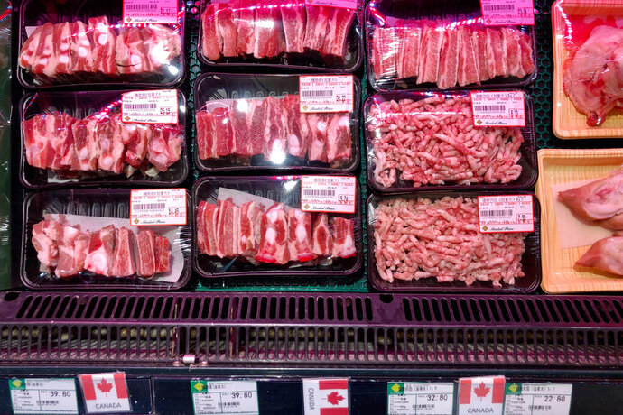 Packs of Canadian pork are displayed for sale at a supermarket in Beijing, Tuesday, June 18, 2019. China will halt imports from a Canadian company after food safety issues were detected in one batch of pork, the Xinhua state news agency reported Tuesday, a move likely to fuel further speculation that China is retaliating against Canada after it arrested a Chinese tech executive. (AP Photo/Andy Wong)