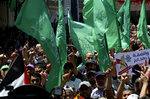 Hamas supporters wave their green and national flags during a protest against Israel's plan to annex parts of the West Bank and U.S. President Donald Trump's mideast initiative, after Friday prayer at the main road of Rafah refugee camp, Gaza Strip, Friday, July 3, 2020. (AP Photo/Adel Hana)