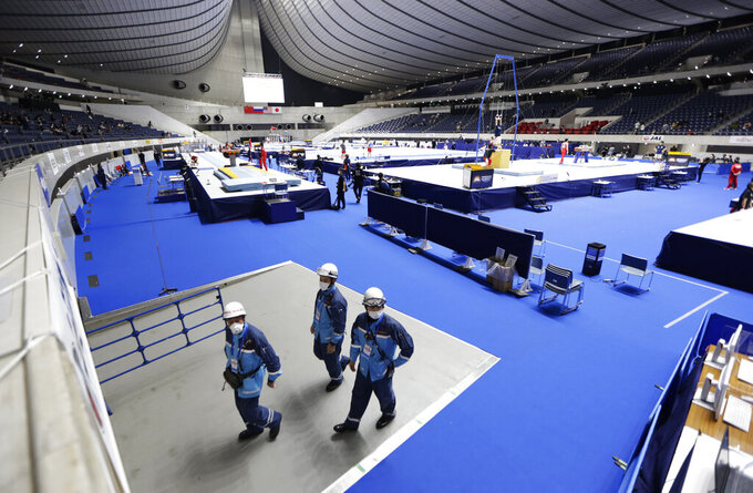 Firefighters walk around the floor of Yoyogi National Stadium First Gymnasium before an international gymnastics meet in Tokyo on Sunday, Nov. 8, 2020. Gymnasts from four countries of China, Russia, U.S. and Japan performed in the meet at the gymnasium, a venue planned to be used in the Tokyo 2020 Olympics in the summer 2021. (AP Photo/Hiro Komae)