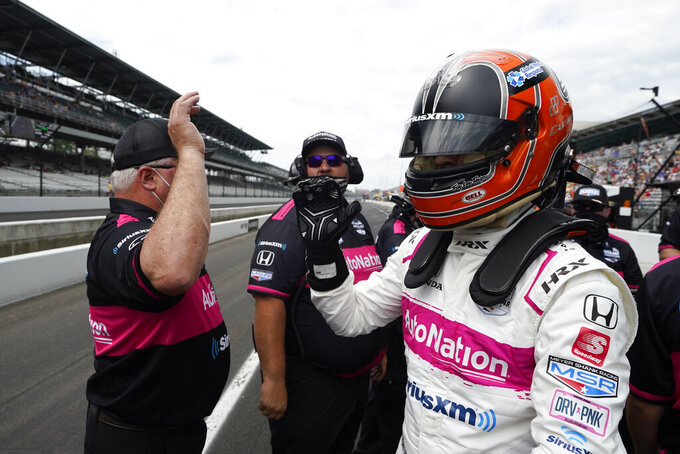 Helio Castroneves, of Brazil, greets his crew members during qualifications for the Indianapolis 500 auto race at Indianapolis Motor Speedway, Sunday, May 23, 2021, in Indianapolis. (AP Photo/Darron Cummings)