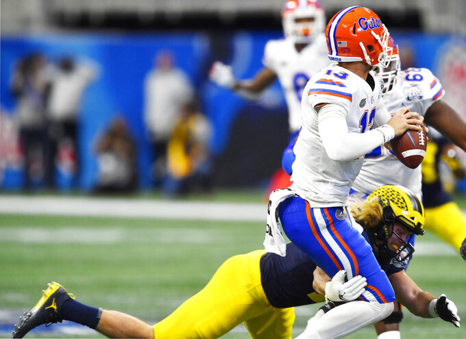 Michigan defensive lineman Luiji Vilain (18) defends against Florida quarterback Feleipe Franks (13) during the first half of the Peach Bowl NCAA college football game, Saturday, Dec. 29, 2018, in Atlanta. (AP Photo/Mike Stewart)