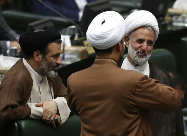 In this Wednesday, May, 27, 2020 photo, Iranian lawmaker Mojtaba Zolnouri, right, who is the head of the influential parliamentary committee for national security and foreign policy, speaks with his colleagues during the inauguration of the new parliament in Tehran, Iran. Zolnouri said Monday, June 1, 2020, that 230 people were killed November's anti-government protests in Iran, which were among the worst the country has seen since its 1979 Islamic Revolution. (AP Photo/Vahid Salemi)