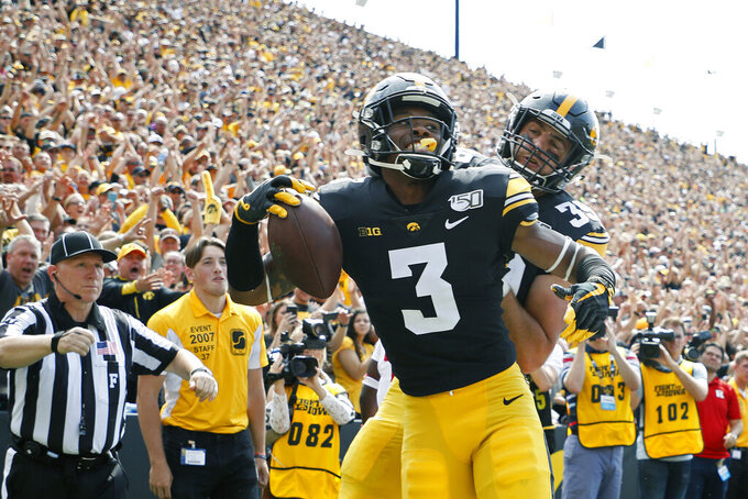 FILE - In this Sept. 7, 2019, file photo, Iowa wide receiver Tyrone Tracy, left, celebrates his touchdown reception with Iowa tight end Nate Wieting, right, during the first half of an NCAA college football game against Rutgers, in Iowa City. No. 19 Iowa's passing game has been lethal so far _ despite losing two first-round picks in tight ends T.J. Hockenson and Noah Fant.(AP Photo/Matthew Putney, File)