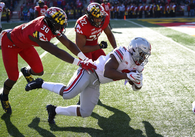 Ohio State running back J.K. Dobbins, front, dives for yardage against Maryland linebacker Isaiah Davis (22) and linebacker Durell Nchami (30) during the first half of an NCAA football game, Saturday, Nov. 17, 2018, in College Park, Md. (AP Photo/Nick Wass)