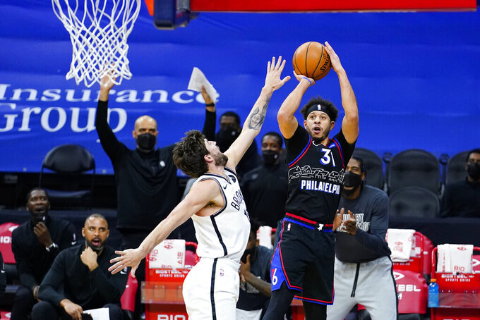 Philadelphia 76ers' Seth Curry (31) goes up for a shot against Brooklyn Nets' Joe Harris (12) during the second half of an NBA basketball game, Saturday, Feb. 6, 2021, in Philadelphia. (AP Photo/Matt Slocum)