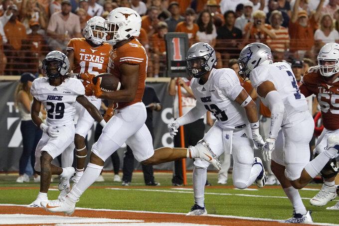 Texas running back Bijan Robinson (5) runs for a touchdown against Rice during the first half of an NCAA college football game Saturday, Sept. 18, 2021, in Austin, Texas. (AP Photo/Chuck Burton)