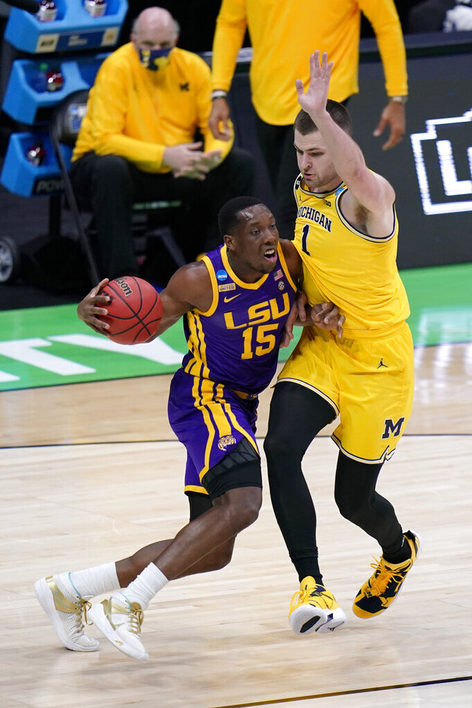 LSU guard Aundre Hyatt (15) drives past Michigan center Hunter Dickinson (1) during the first half of a second-round game in the NCAA men's college basketball tournament at Lucas Oil Stadium Monday, March 22, 2021, in Indianapolis. (AP Photo/AJ Mast)