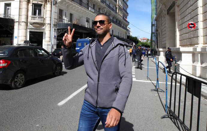 FILE - In this March 10, 2020 file photo, Algerian journalist Khaled Drareni flashes the V sign as he leaves the courthouse in Algiers. An Algerian court sentenced on Tuesday journalist Khaled Drareni to two years in prison on appeal, in a trial that rights group have denounced as violating press freedom. Drareni, editor of the Casbah Tribune news site and Algeria correspondent of RSF and the French TV channel TV5 Monde, played a prominent role in covering the country's pro-democracy movement last year.(AP Photo/Str, File)