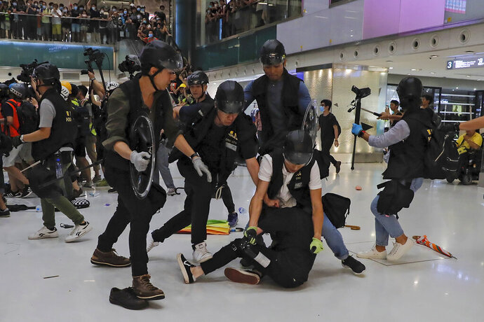 A protester is tackled by policemen after a scuffle inside a shopping mall in Sha Tin District in Hong Kong, Sunday, July 14, 2019. Police in Hong Kong have fought with protesters as they broke up a demonstration by thousands of people demanding the resignation of the Chinese territory's chief executive and an investigation into complains of police violence. (AP Photo/Kin Cheung)