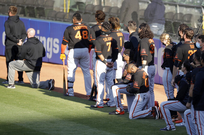 San Francisco Giants' Antoan Richardson (00) and Jaylin Davis kneel during the national anthem prior to an exhibition baseball game against the Oakland Athletics, Monday, July 20, 2020, in Oakland, Calif. (AP Photo/Ben Margot)
