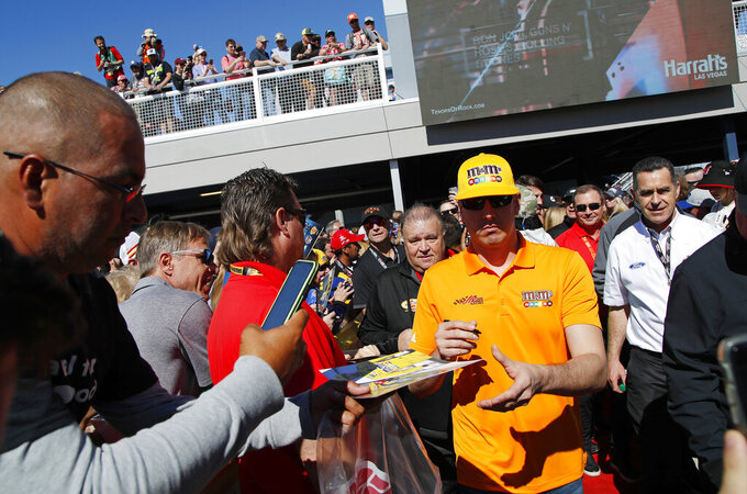 Kyle Busch, center right, gives autographs to fans before a NASCAR Cup Series auto race at Las Vegas Motor Speedway, Sunday, March 3, 2019, in Las Vegas. (AP Photo/John Locher)