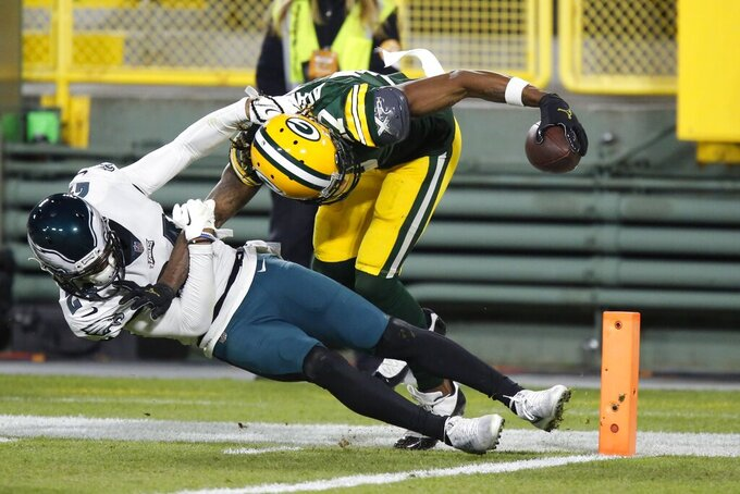 Green Bay Packers' Davante Adams catches a touchdown pass with Philadelphia Eagles' Darius Slay defending during the second half of an NFL football game Sunday, Dec. 6, 2020, in Green Bay, Wis. The pass was Aaron Rodgers' 400th career touchdown pass.(AP Photo/Matt Ludtke)