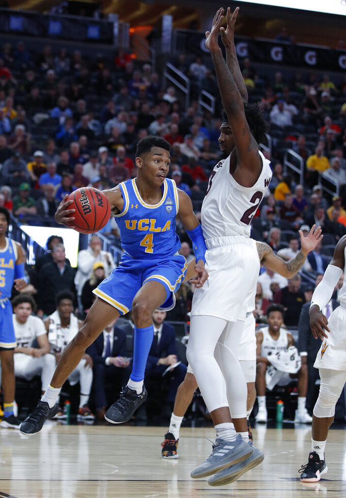 UCLA's Jaylen Hands passes around Arizona State's Romello White during the first half of an NCAA college basketball game in the quarterfinals of the Pac-12 men's tournament Thursday, March 14, 2019, in Las Vegas. (AP Photo/John Locher)