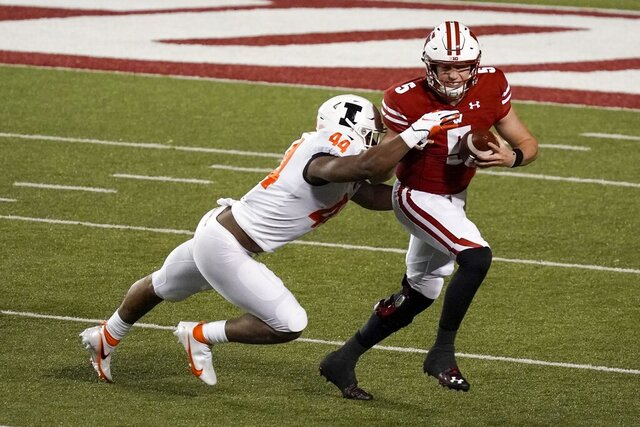 Wisconsin's Graham Mertz tries to run past Illinois's Tarique Barnes during the first half of an NCAA college football game Friday, Oct. 23, 2020, in Madison, Wis. (AP Photo/Morry Gash)