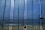 In this Sunday, July 14, 2019, file photo, two man walk at Sijung Ho beach against a plastic curtain outside a restaurant in North Korea. The beach is a popular tourist destination for locals and foreigners alike. (AP Photo/Vincent Yu, File)