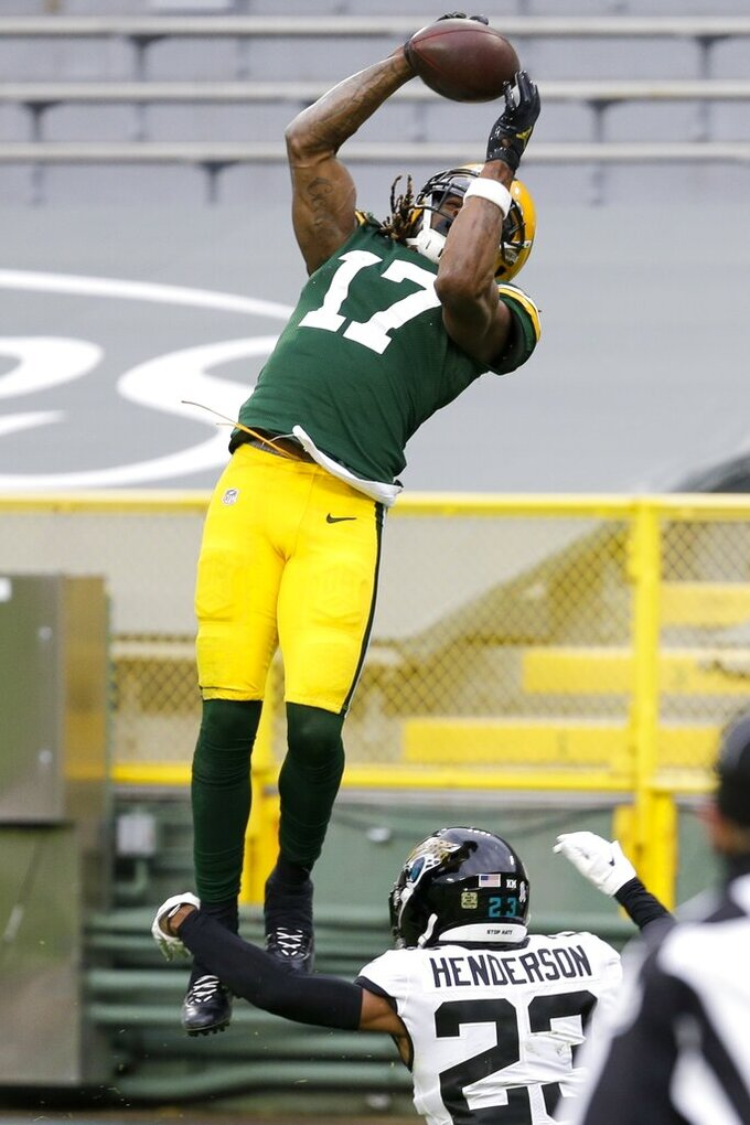 Green Bay Packers' Davante Adams goes over Jacksonville Jaguars' C.J. Henderson for a touchdown catch during the second half of an NFL football game Sunday, Nov. 15, 2020, in Green Bay, Wis. The Packers won 24-20. (AP Photo/Mike Roemer)