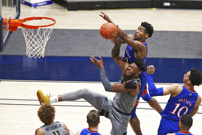 West Virginia forward Derek Culver (1) and Kansas guard Ochai Agbaji (30) go for a rebound during the first half of an NCAA college basketball game Saturday, Feb. 6, 2021, in Morgantown, W.Va. (AP Photo/Kathleen Batten)