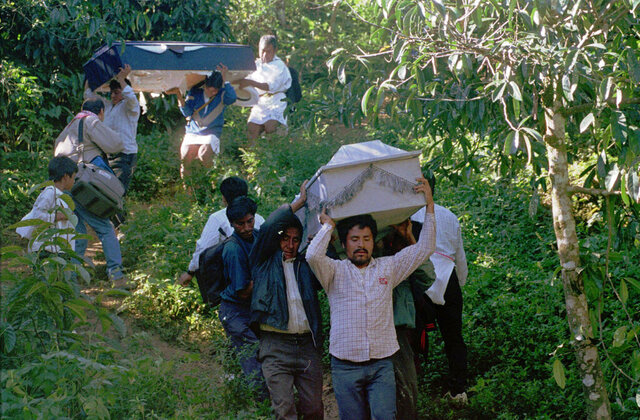 FILE - In this Dec. 25, 1997 file photo, family members carry coffins of victims killed in a massacre in Acteal, in the remote highlands of the southeastern Mexican state of Chiapas. The Mexican government said Thursday, July 23, 2020, that it will build as many as 20 public works projects in the area that was the scene of the 1997 massacre of 45 indigenous villagers. (AP Photo/Elizabeth Dalziel, File)