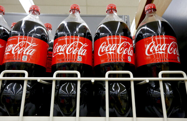 FILE- In this Aug. 8, 2018, file photo bottles of Coca-Cola sit on a shelf in a market in Pittsburgh.  The Coca-Cola Co. said on Thursday, Oct. 22, 2020, it saw gradual improvement in the third quarter, as it turned its focus to emerging leaner from the global pandemic. Atlanta-based Coke said its revenue fell 9% to $8.7 billion.  (AP Photo/Gene J. Puskar, File)